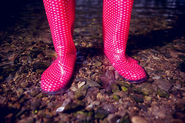 Low section of a woman in pink gumboots on pebbles