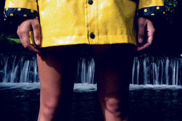 Woman in yellow raincoat against scenic waterfall