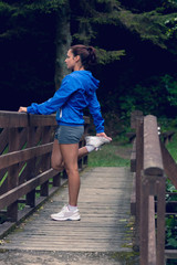 Healthy woman stretching her leg during exercise on footbridge