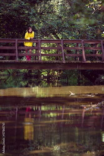 Woman on footbridge over lake and amid foliage