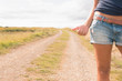 Mid section of woman hitchhiking on dirt countryside road