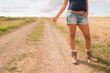 Cool woman hitchhiking on dirt countryside road