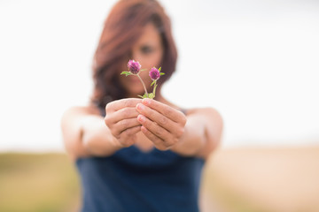 Blurred woman holding out wild flowers against clear sky