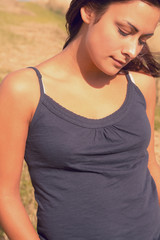 Thoughtful woman in tank top looking down at field