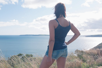 Rear view of young woman standing by sea