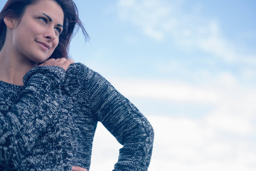 Thoughtful smiling woman in sweater against sky
