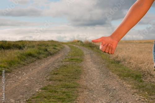 Woman hitchhiking on dirt countryside road