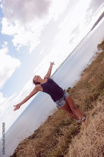 Woman with hands outstretched by the sea