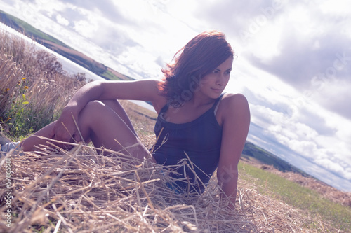 Beautiful relaxed woman sitting by sea against cloudy sky