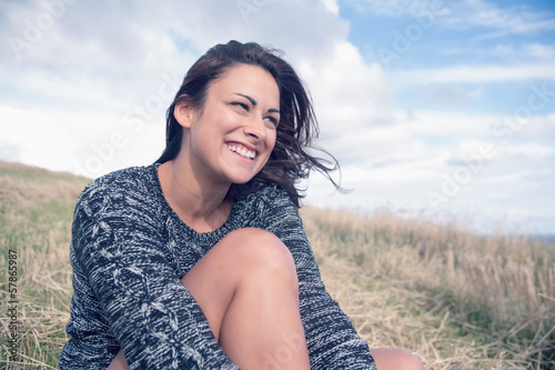 Thoughtful happy woman sitting at field against sky