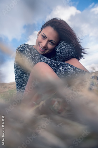 Happy young woman sitting at field against sky