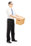 Full length portrait of a smiling  man giving a box to someone