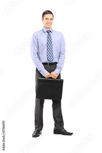 Full length portrait of a businessman holding a leather suitcase