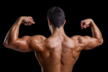 Muscle young man showing his back muscles against a dark backgro