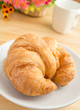 Closeup of a croissant with coffee cup