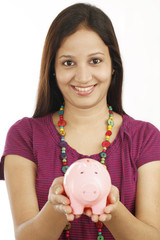 Young Indian woman holding a piggy bank