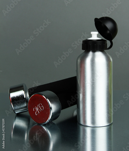 Sports bottle and dumbbells on grey background