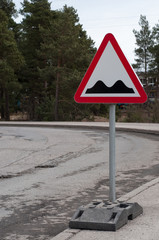 Sign and potholes on the road