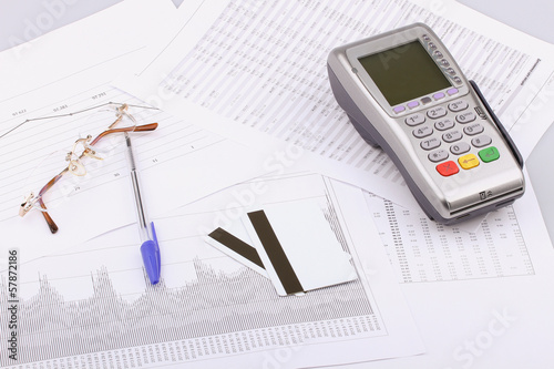 Business still-life of pen, eyeglasses, terminal, credit Cards