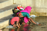 Indian woman with her daughter washing clothes in lake