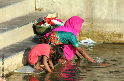 Foto op Canvas India Indian woman with her daughter washing clothes in lake