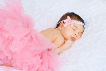 Little girl in a pink skirt is sleeping on the stomach