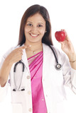 Happy Indian doctor woman showing red apple