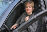 Safe driving, mid adult Caucasian woman fastening seat belt