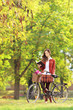Young woman with bicycle in a park reading book