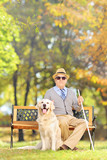 Senior blind man sitting on a bench with his dog, in a park