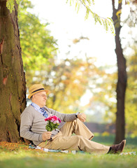 Gentleman with flowers sitting on a grass and checking the time