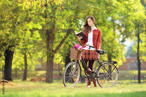 Young female with bicycle in a park reading book