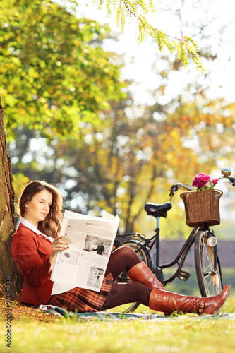 Young woman with bike sitting and reading a newspaper in park