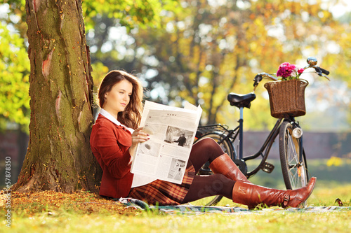 Young woman with bicycle sitting on grass and reading newspaper