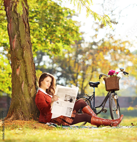 Woman with bicycle sitting on a grass and reading a newspaper