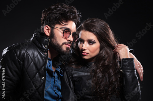 pensive man with glasses and long beard embracing his girlfriend