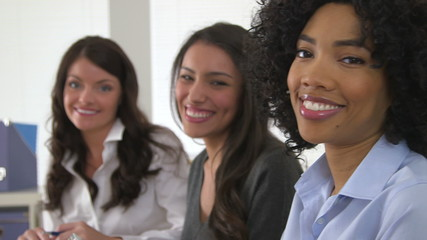 Close up of three business women smiling together in office