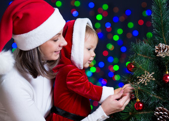 baby girl with mother decorating Christmas tree on bright backgr