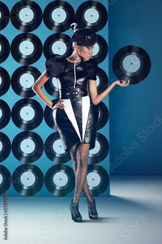 Disco african women stands with vinyl records on the wall