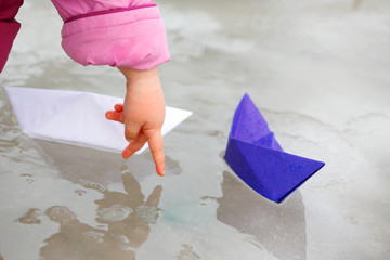 Two paper ship in puddle and child's hand