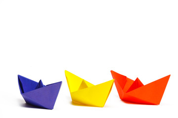Three colored paper ship on a white background