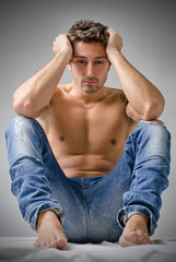 Sad or depressed young man shirtless, sitting on the floor