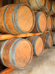 Stack of round wooden wine barrels in cellar shelf.