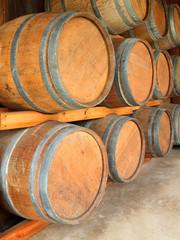 Stack of round wooden wine barrels in cellar shelf.