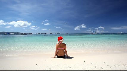 Woman in Santa Claus hat sitting on tropical beach, Boracay, Phi