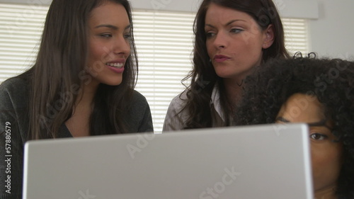 Three business women discussing work and using laptop computer
