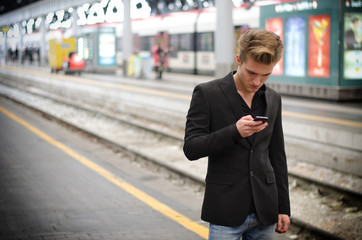 Attractive blond young man in station using cellphone