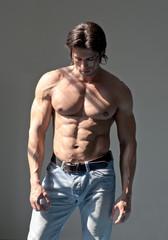 Handsome muscular man shirtless on grey background
