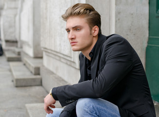 Attractive blond young man in jeans and jacket, sitting outdoors