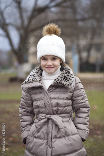 Little girl in a white knitted hat autumn